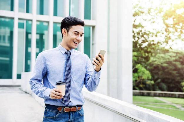 Gelukkige jonge zakenman die een slimme telefoon met behulp van openlucht