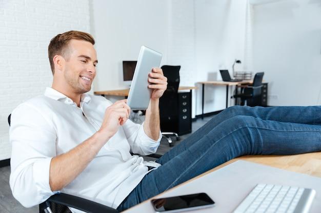 Gelukkige jonge zakenman die met benen op tafel zit en tablet gebruikt op de werkplek