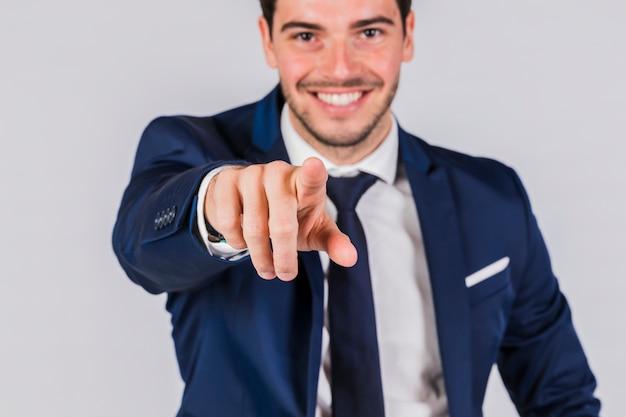 Gelukkige jonge zakenman die zijn vinger op camera op grijze achtergrond richten