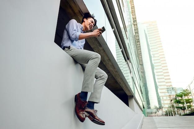 Gelukkige jonge zakenman in vrijetijdskleding die mobiele telefoon met behulp van terwijl het zitten door het stedelijke gebouw.