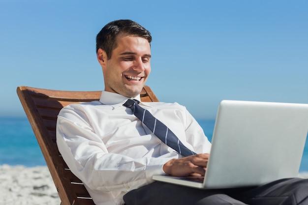 Gelukkige jonge zakenman op een ligstoel die zijn computer met behulp van