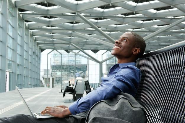 Gelukkige jonge zakenman zit met laptop op station
