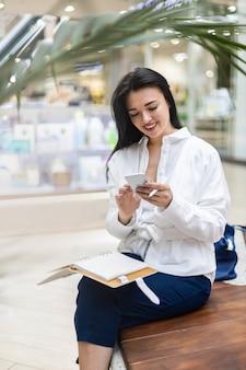 Gelukkige jonge zakenvrouw die aan het chatten is, gebruikt een smartphone in de hal van het moderne winkelcentrum