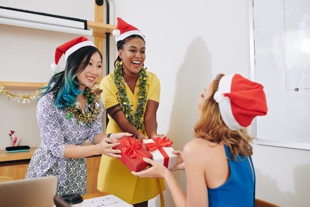 Gelukkige jonge zakenvrouw die kerstcadeautjes accepteert van haar medewerkers met kerstmutsen
