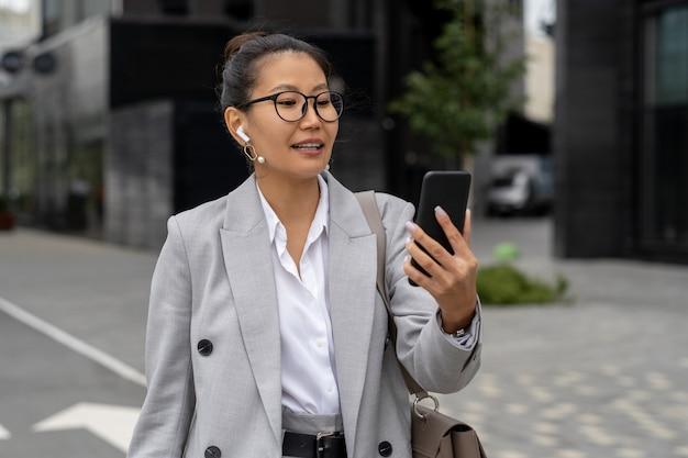 Gelukkige jonge zakenvrouw maakt videogesprek terwijl ze door straat loopt