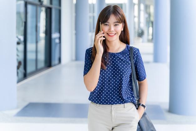 Gelukkige jonge zelfverzekerde aziatische zakenvrouw die aan de telefoon praat terwijl ze buiten haar kantoor loopt