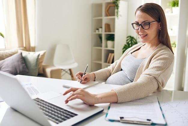 Gelukkige jonge zwangere onderneemster die laptopvertoning bekijkt en notities maakt in kladblok tijdens het analyseren van financiële informatie