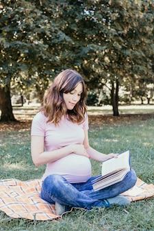 Gelukkige jonge zwangere vrouw die een boek leest in het park op een lente- of zomerdag.