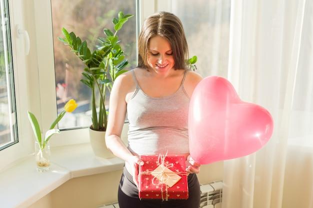 Gelukkige jonge zwangere vrouw met giftdoos en hartballon