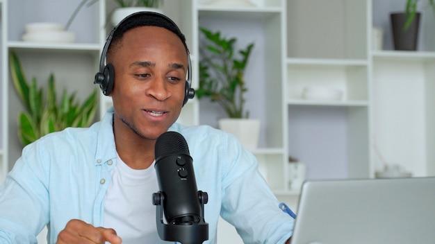 Gelukkige jonge zwarte mannelijke audioblogger die hoofdtelefoons met een laptopcomputer en microfoonuitzendingen in een thuiskantoor draagt