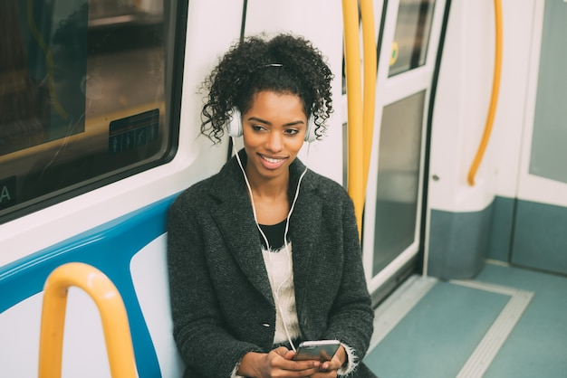 Gelukkige jonge zwartezitting binnen ondergronds luisterend aan muziek