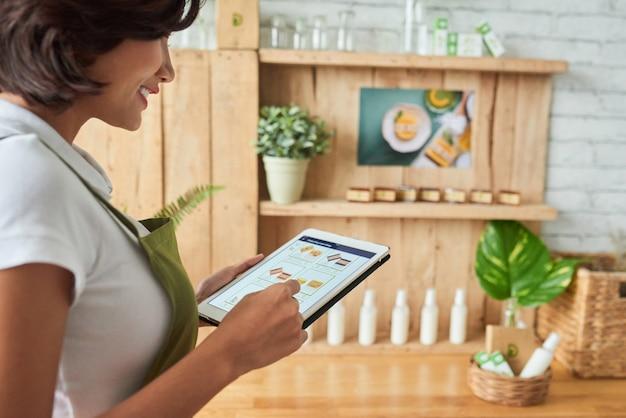 Gelukkige jongedame die foto's uploadt van zeep die ze via tabletcomputer in de online winkel heeft gemaakt