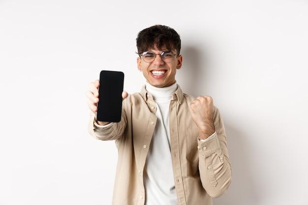Gelukkige jongeman die online prijs wint, smartphonescherm laat zien en zich verheugt over goed nieuws, gelukkig op witte muur staat.