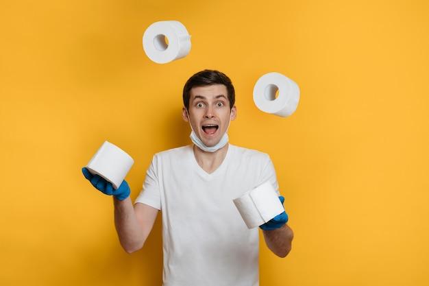 Gelukkige jongeman jongleert met rollen wc-papier, voelt zich veilig als het coronavirus thuis blijft.