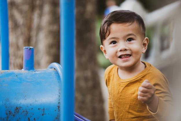 Gelukkige jongen buiten spelen in het park
