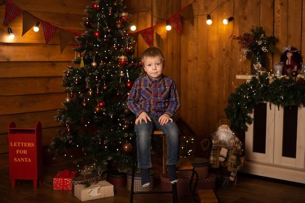Gelukkige jongen dichtbij kerstboom. kleine jongen zittend in een stoel in de buurt van de kerstboom.