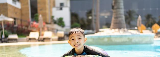 Gelukkige jongen die bij het zwembad speelt, glimlacht en naar de camera kijkt, panorama met kopieerruimte