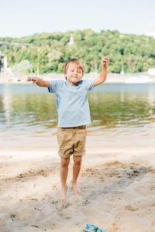 Gelukkige jongen die bij zandige kust springt
