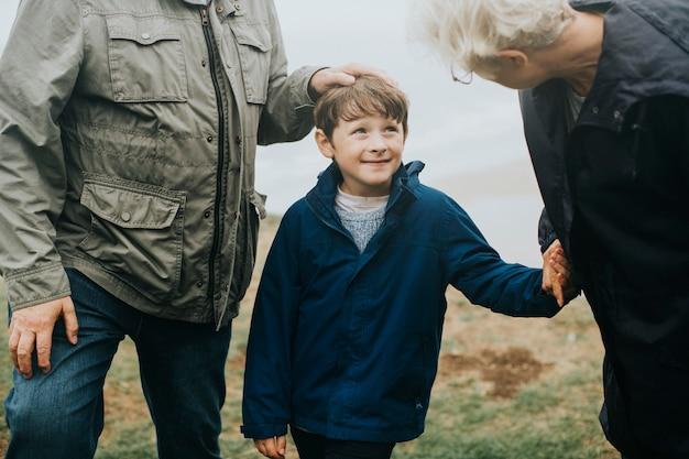 Gelukkige jongen die door het strand met zijn grootouders loopt