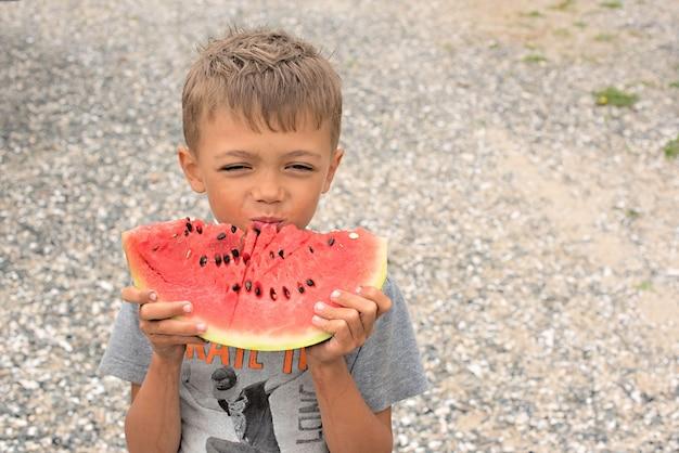 Gelukkige jongen die een rijpe watermeloen eet.