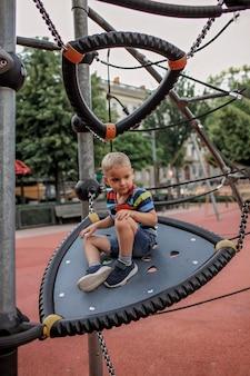 Gelukkige jongen die een rust op de speelplaats in lokaal park hebben tijdens haar die reizen