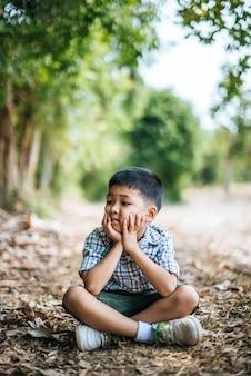 Gelukkige jongen die en alleen in het park zitten denken