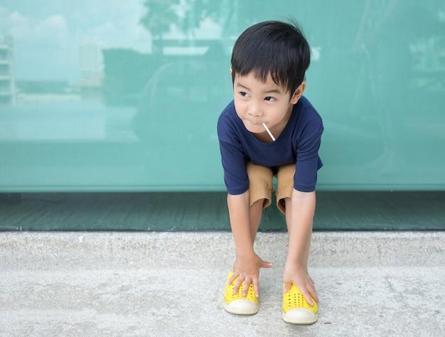 Gelukkige jongen die en het suikergoedzitting van lollys glimlacht eet met blauwe achtergrond