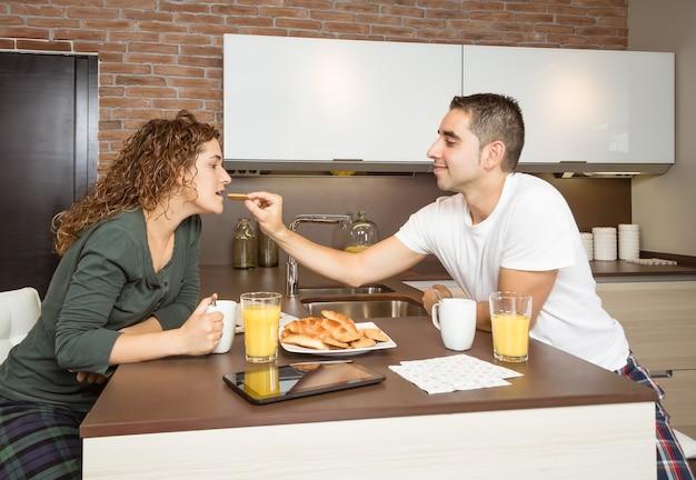 Gelukkige jongen die haar vriendin voedt met een ontbijt