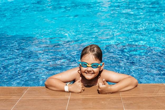 Gelukkige jongen die in de pool zwemt