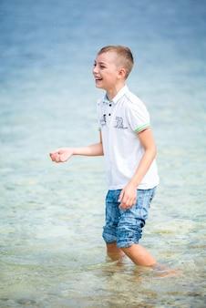 Gelukkige jongen die in de zomer voor de zee staat