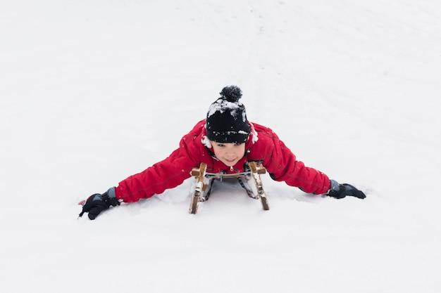 Gelukkige jongen die op slee naar beneden in sneeuwlandschap sleeën