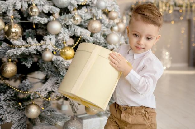 Gelukkige jongen die op vloer met kerstmisgiften legt in verfraaide ruimte