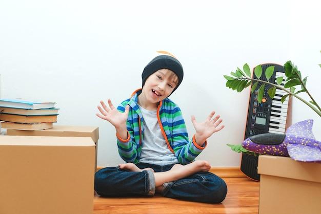 Gelukkige jongen die plezier heeft in de verhuisdag. huisvesting van een jong gezin met kind. familie verhuist naar een nieuw appartement.