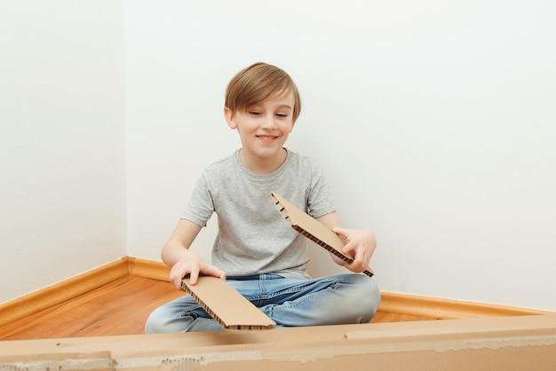 Gelukkige jongen die pret heeft. leuk kind dat dozen helpt uitpakken.