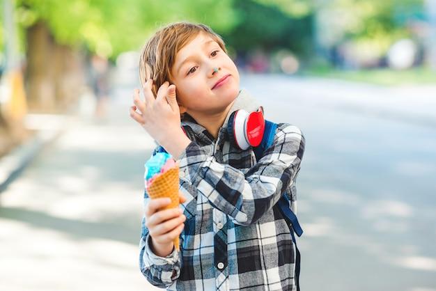 Gelukkige jongen die roomijs in openlucht eet. kid wandelen in het park in zonnige dag. stijlvolle jongen buitenshuis.