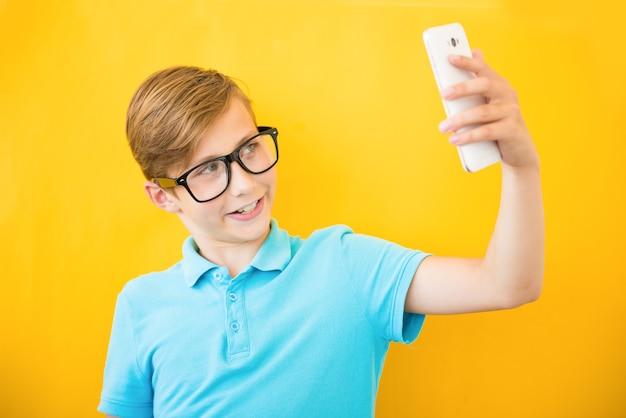 Gelukkige jongen die selfie op gele achtergrond maakt