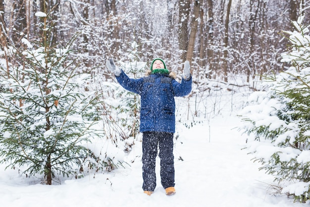 Gelukkige jongen die sneeuw werpt. kind, seizoen en winter concept.