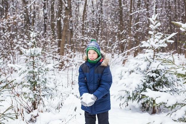 Gelukkige jongen die sneeuw werpt. kind, seizoen en winterconcept.