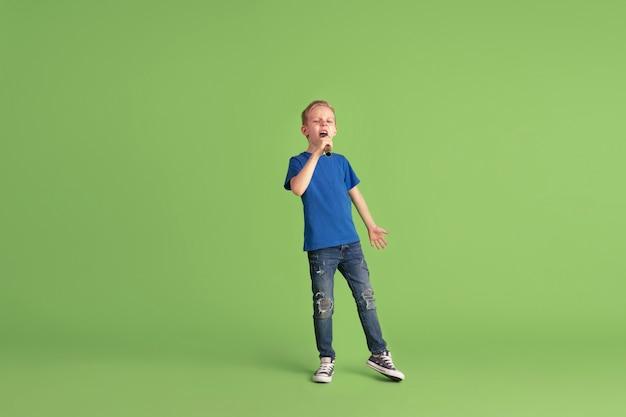 Gelukkige jongen die speelt en plezier heeft op de groene studiomuur