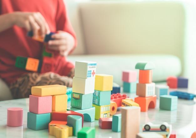 Gelukkige jongen die stuk speelgoed blokken op een woonkamer voor onderwijsspeeltje stapelen