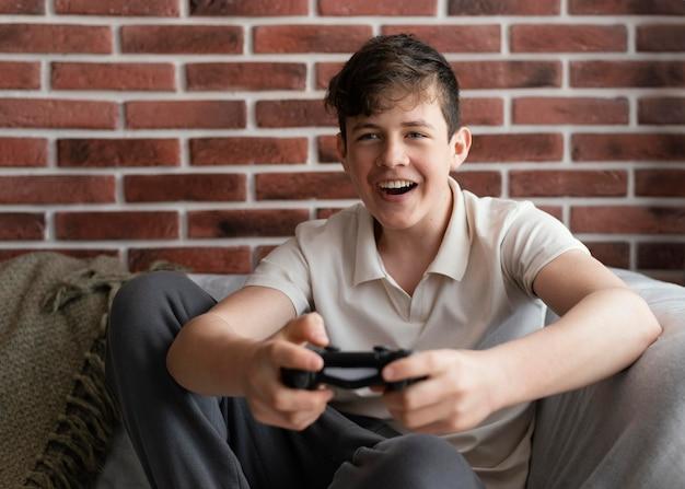 Gelukkige jongen die videogame speelt
