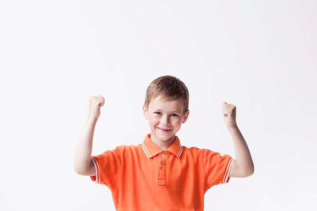 Gelukkige jongen die vuist dichtklemmen die ja gebaar op witte muur maken