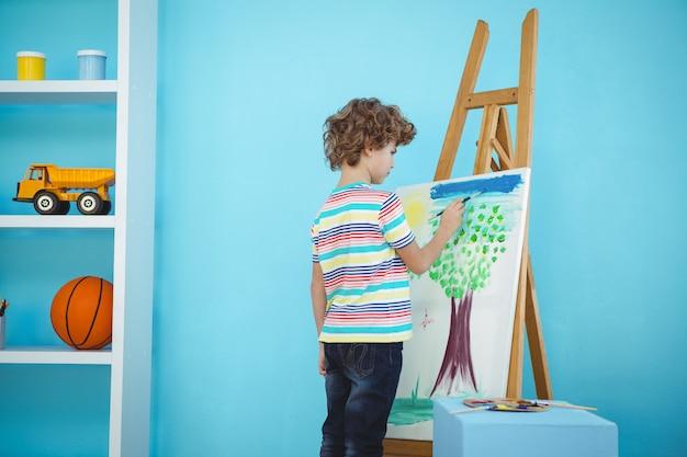 Gelukkige jongen die zijn beeld op een schildersezel schildert