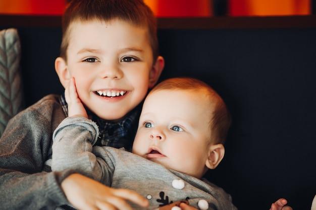 Gelukkige jongen die zijn kleine broertje omhelst.