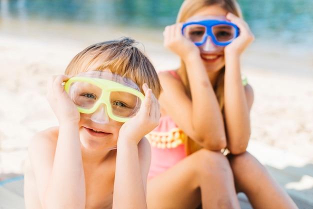 Gelukkige jongen en glimlachende vrouw die in beschermende brillen op zandkust zitten