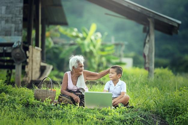 Gelukkige jongen en grootmoeder die laptop in openlucht met behulp van