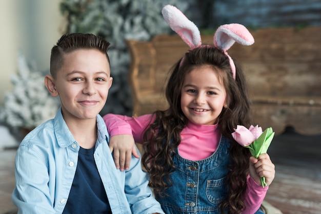 Gelukkige jongen en meisje in konijntjesoren met tulpen