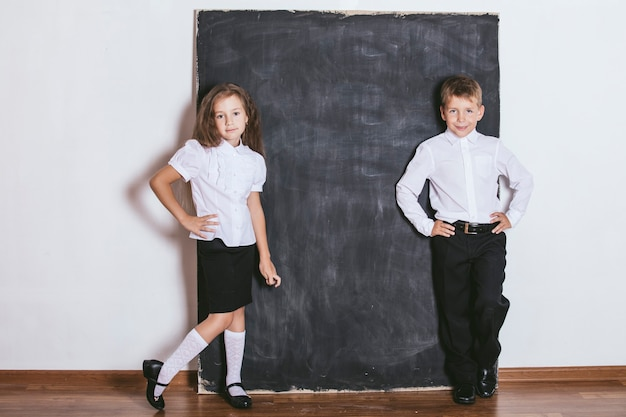 Gelukkige jongen en meisje van de basisschool op de achtergrond van de klas