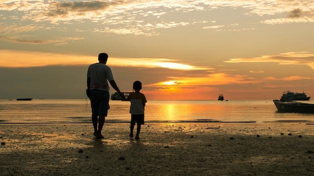 Gelukkige jongen en vader die op de achtergrond van de strandzonsondergang lopen