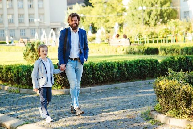 Gelukkige jongen en vader die samen plezier hebben tijdens een wandeling. knappe vader en kind stijlvolle pakken dragen.